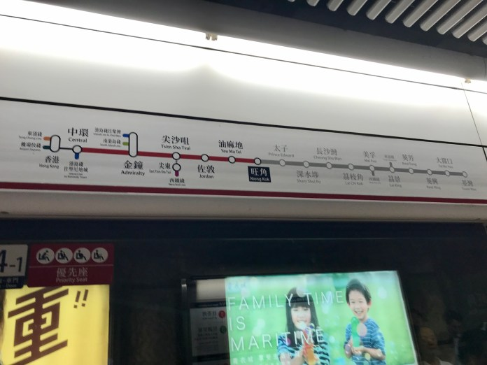 A decal sign above platform doors showing location-relevant information at Mong Kong Station in Hong Kong's MTR metro system.