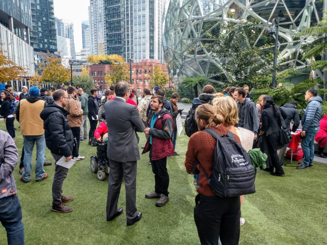 An Amazon contract employee who opposed Amazon's copious campaign spending talks to a reporter. before an October 24th rally at the Amazon Spheres. (Photo by author)