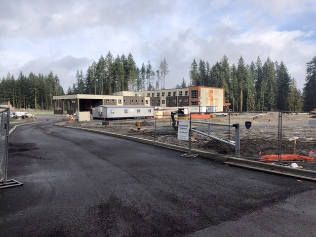 Photograph of the new Ruby Bridges elementary school under construction. Most of the building is up with a lot of site work to be done.