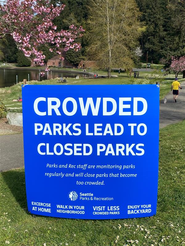 """Crowded parks lead to closed parks,"" reads the City's sign at Seward Park, suggesting people stay home or in their yards instead."