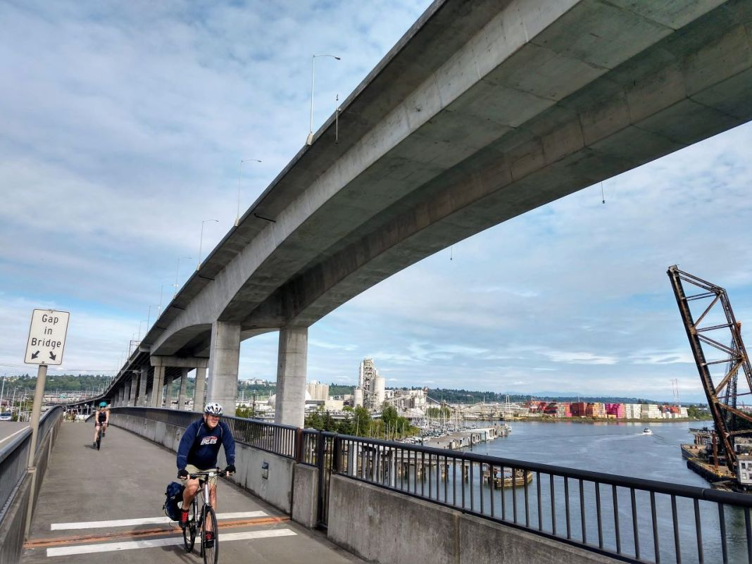 People bike on the low bridge with the cracked high bridge looming overhead. (Photo by Doug Trumm)