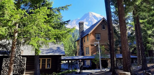 Some Douglas firs and Mount Tahoma frame National Park Inn wooden lodge in Longmire.