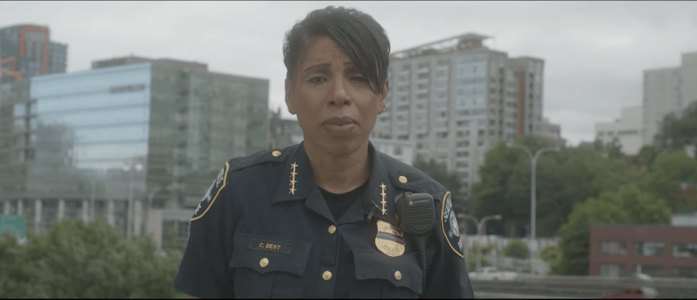 Chief Best with a Downtown Seattle buildings and street behind her. Video is here: https://www.seattle.gov/police/together