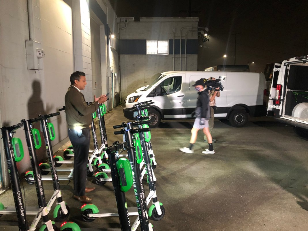 A reporter stands amidst scooters in a garage for a TV spot.