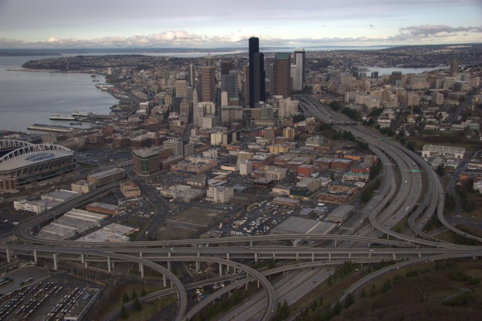 A birds eye view of Downtown Seattle from the south with the I-5 and I-90 spaghetti interchange dominating the frame.