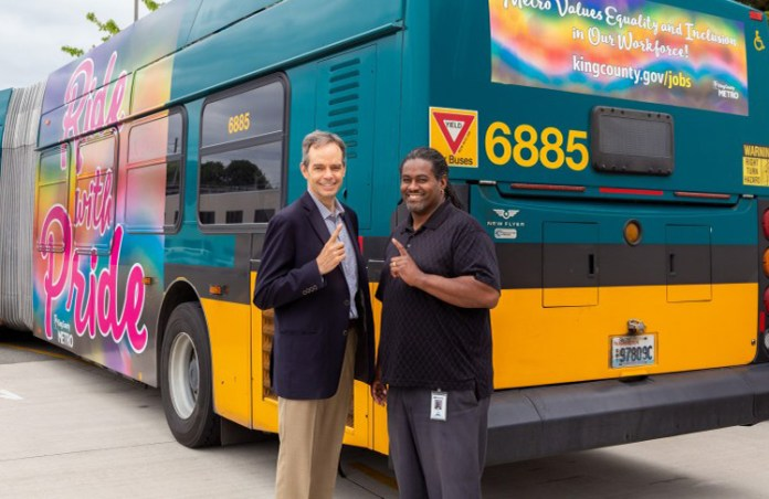 A Metro bus with a rainbow Pride wrap is the backdrop for Metro executives Rob Gannon and White.