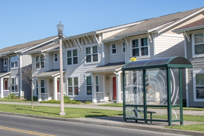 A rowhouse with a transit shelter.