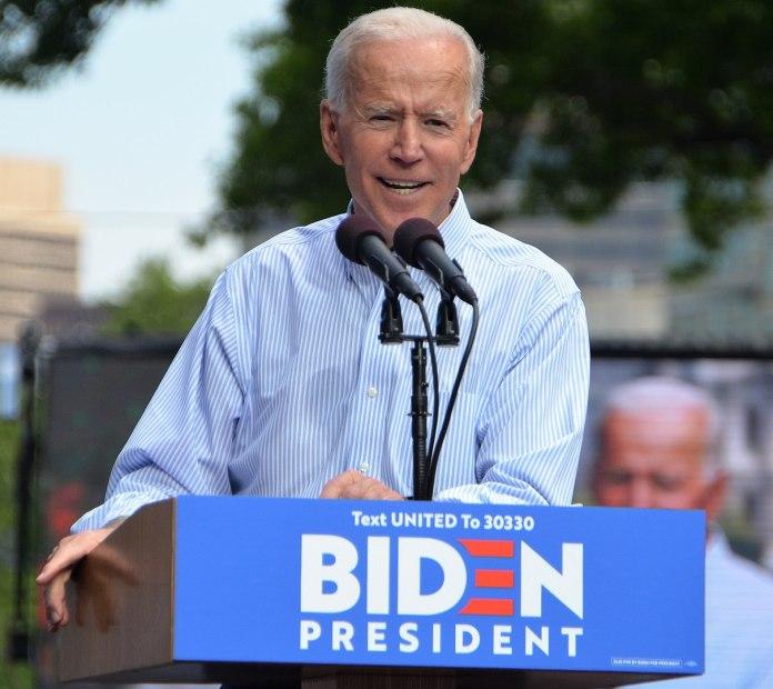 Joe Biden in a blue collar behind a lectern with Biden for President on it.