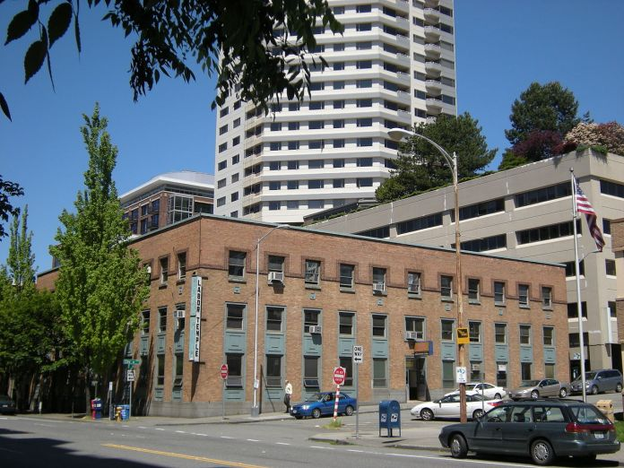 The three story brick labor temple with teal accents. A Belltown skyscraper is in the background.