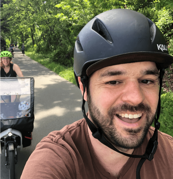 Tom taking a selfie biking on a trail with Kelli and the kid in tow