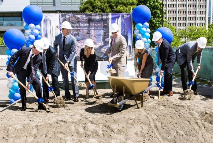 Developers in suits shovel dirt into a wheelbarrow next to a sign showing the future Lincoln Square towers.