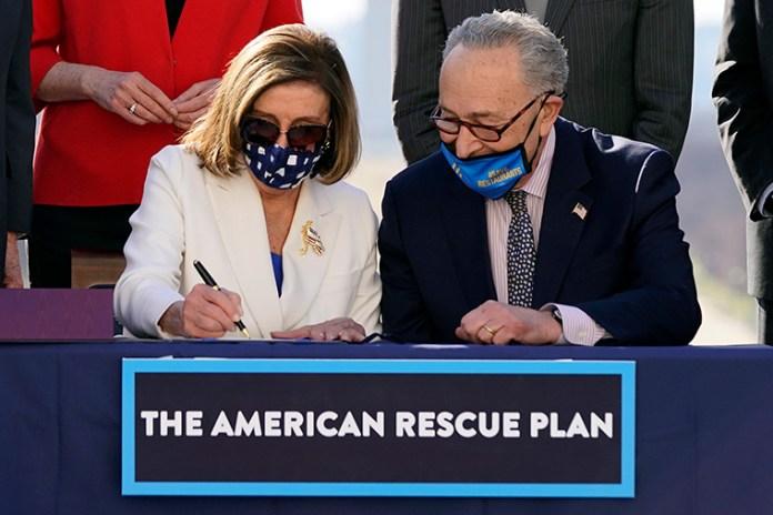 House Speaker Nancy Pelosi of California signs the $1.9 trillion COVID-19 relief bill. (Courtesy of AP Photo/Alex Brandon)