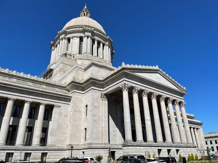 The Capitol building in Olympia is marble colored and include pillars and a dome in the classic style.