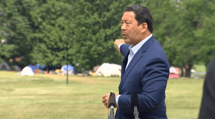 Harrell wears a blazer and gestures toward tents in the background.