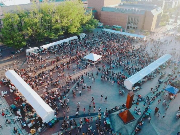 A busy UW Night Market in Red Square on the university campus. Vendor tents are located on the exterior of the square as pedestrians crowd the center area.