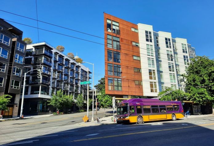 A Route 33 trolley bus at the intersection 1st Avenue and Denny Way with low-rise apartment buildings behind.