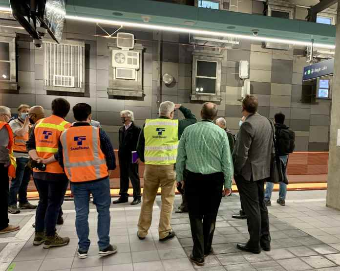 A group of men wearing colorful Sound Transit vests and suits stand at the station platform and look at the metal wall with architectural fragment inspired sculptures.
