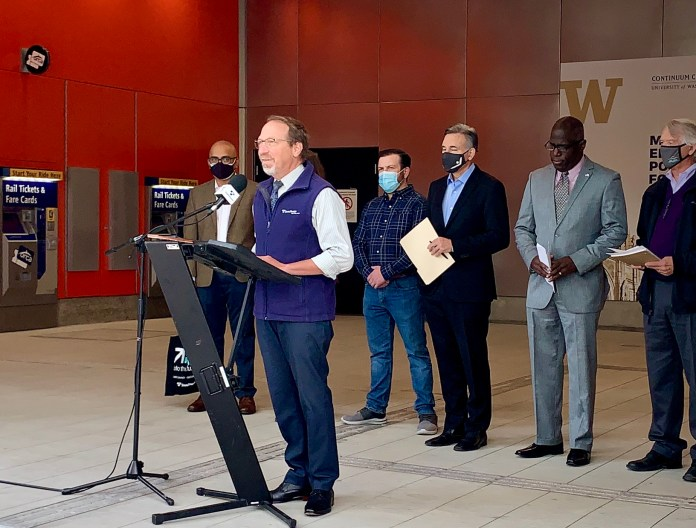A photo of a White man standing at a podium wearing a blue Sound transit vest. A group of men stand behind him at the U District station entrance.