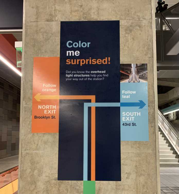 A wayfinding sign shows riders to follow the orange arrows and lights to the north exit at Brooklyn Street and the teal arrows and lights to the South exit at 43rd St.