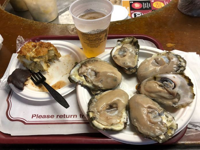 A photo of a tray of food with a plate of oysters and crab cake on it.