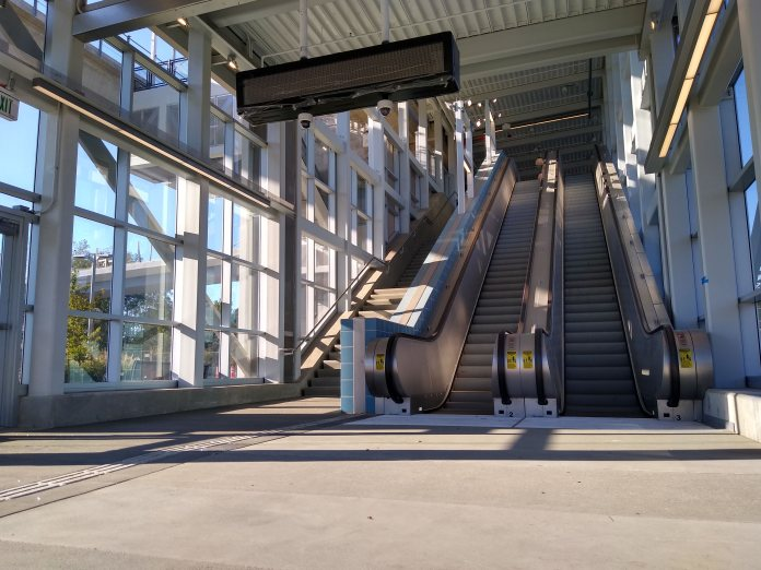 Two escalators and a stairway at a light rail station entrance