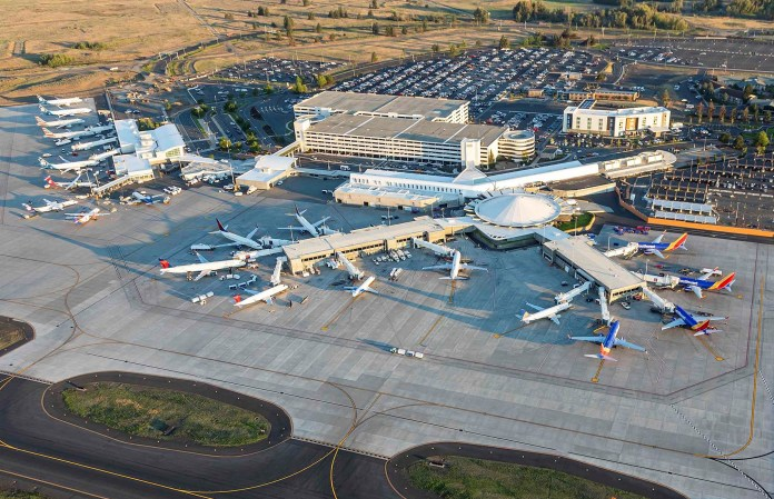 An photo showing an aerial view of the Spokane airport terminal and runway with planes.