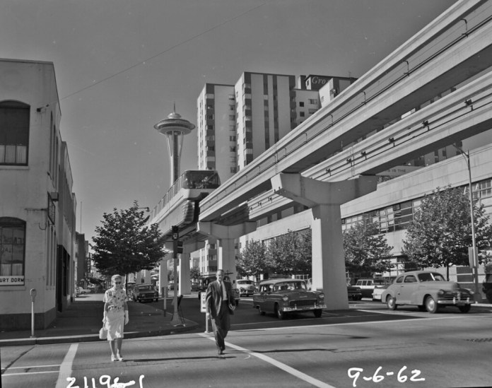 A black and white photograph of a monorail train running above a street in Downtown Seattle with a man and woman crossing beneath on foot at a crosswalk.