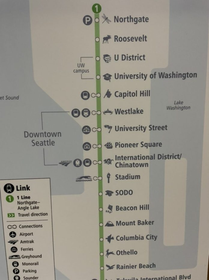 A vertical version of a similar diagram for the 1 line shows brackets to indicate the four Downtown Seattle stations and another bracket to indicate the two stops on UW's Seattle campus.