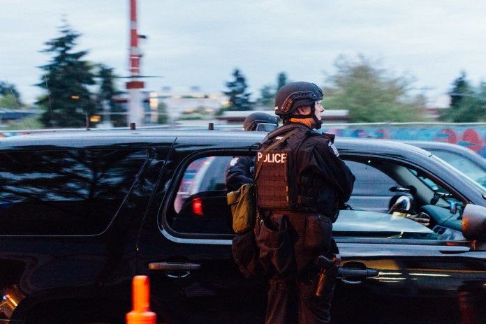 A photo shows a police officer in riot gear standing next to a patrol car.