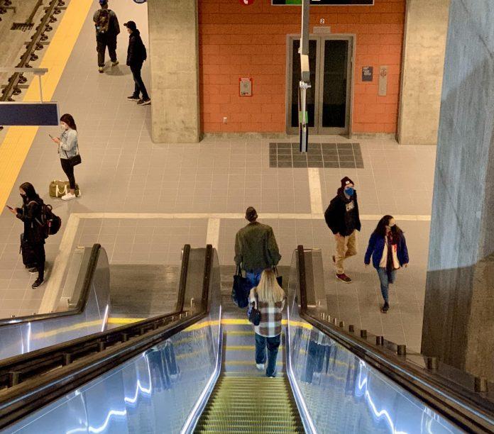 A photo of an illuminated escalator leading down to a light rail platform.