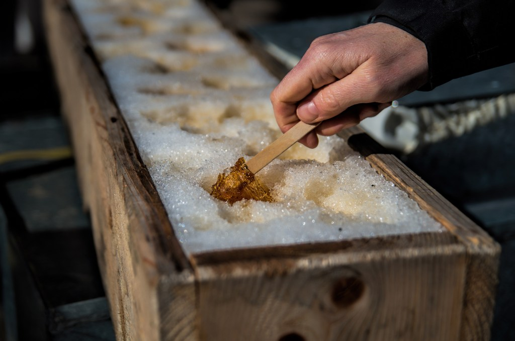 Hand picking maple sugar on snow (Adobe Stock)
