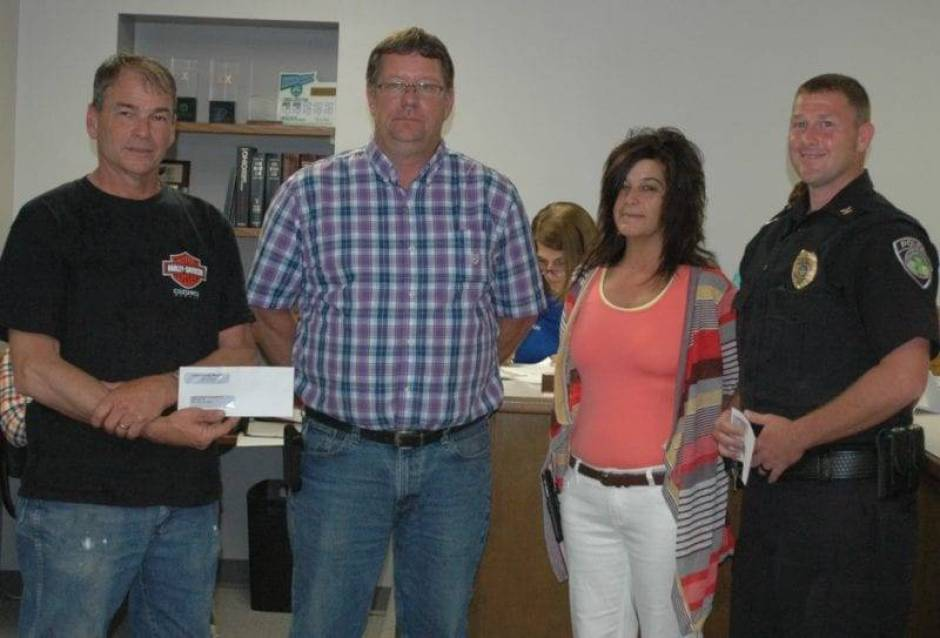Kamco Executive Vice President Alan Benien (left center) and Kamco Plant Manager Lisa Woodring (right center) attended the meeting of the West Unity Village Council to give thanks to the community by donating to both the Brady Township Fire Department, represented by Jim Eisel (left) and the West Unity Police Department, represented by Police Chief J.R. Jones (right).