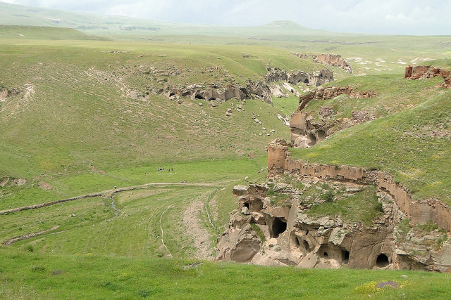 A gorge below Ani, showing numerous caves dug into cliffs, as well as fortifications. Source