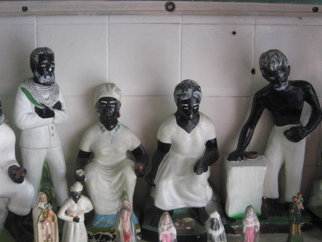 """Small Umbandan statues of pretos velhosor """"old slaves"""", spirits of those who died enslaved. The statues represent suffering, compassion, forgiveness, and hope. The Umbanda religion recognizes Anastacia as a saint and martyr. Photo Credit"""