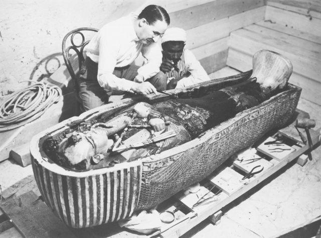 ماہر آثار قدیمہ ہاورڈ کارٹر (1874-191939) تیسری ماں کے سائز والے سرکوفگس کا معائنہ کر رہے ہیں ، 1922۔