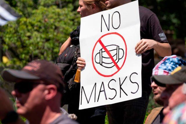 ایک ماسک مخالف نشان تھامے احتجاج کرنے والا۔