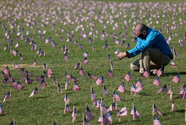 ڈی سی کے نیشنل مال میں ایک شخص منی امریکی پرچموں کے درمیان جھکا ہوا ہے