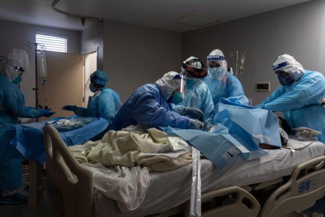 حفاظتی پوشاک میں ڈاکٹر ہسپتال کے بستر پر مریض کی دیکھ بھال کر رہے ہیں۔