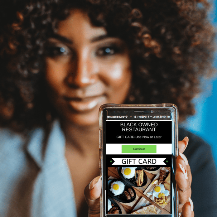 Danielle McGee holds up mobile version of her app Black Business Boom (Courtesy Photo)