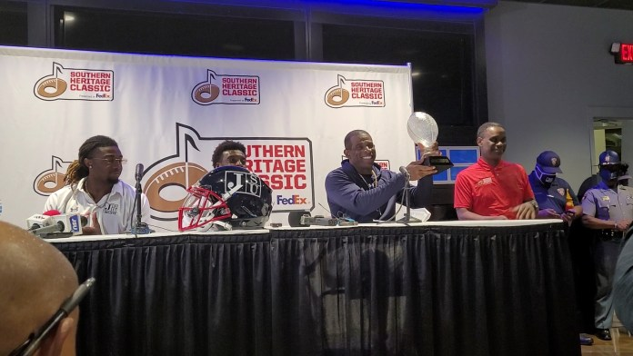 Jackson State Coach Deon Sanders holds up Southern Heritage Classic Trophy.