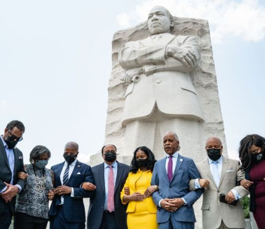Martin Luther King III, his wife Arndrea Waters King, and Rev. Al Sharpton, stand with locked arms praying with Texas Legislative Black Caucus members, from left to right: Sheryl Cole, Jarvis Johnson, Rhetta Andrews Bowers, Ron Reynolds, Carl O. Sherman, Jasmine Crockett, and Shawn Thierry, at the Martin Luther King, Jr. Memorial in Washington, D.C. on July 28. (Cheriss May/Getty Images)
