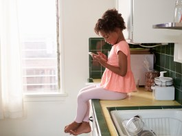 Young Girl Sits In Kitchen And Plays With Mobile Phone. (Photo by: monkeybusiness)