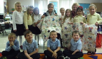 The Kindergarten class presents the quilts that they made to be given to expectant mothers to Mrs. Langdon of the Pregnancy Life Center  (Photo submitted.)