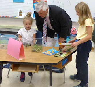 Firstgrade student Mrkynlee Dickinson shares information about the Wooly Bear Caterpillar with Van Wert Mayor Jerry Mazur and fourth grade student Braelynn Burk. (Photo submitted,)
