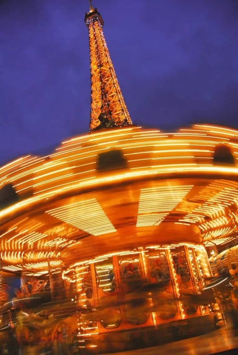 The Eiffel Tower peeking from behind the Carousel on the banks of the Seine River.