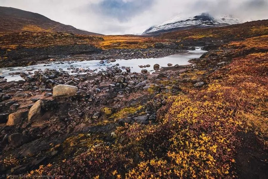 River, autumn colours and snow-covered peak on Disko Island