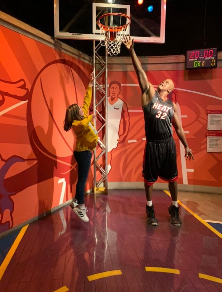Girl with wax figure playing basketball