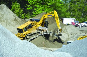 A bulldozer and excavator working on the early stages of the dorms.