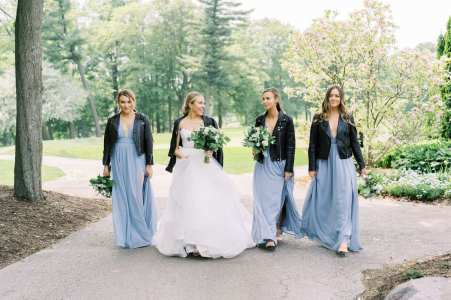 fresh look design bride walking with her bridesmaids dressed in long blue gowns