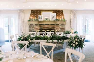 fresh look design white ladder back chairs wedding guest tables with candles and greenery